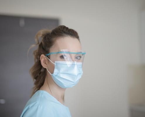 Mujer con mascarilla quirúrgica y escudo facial medidas de prevención Covid