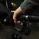 Persona echando bencina a auto en estación de servicio